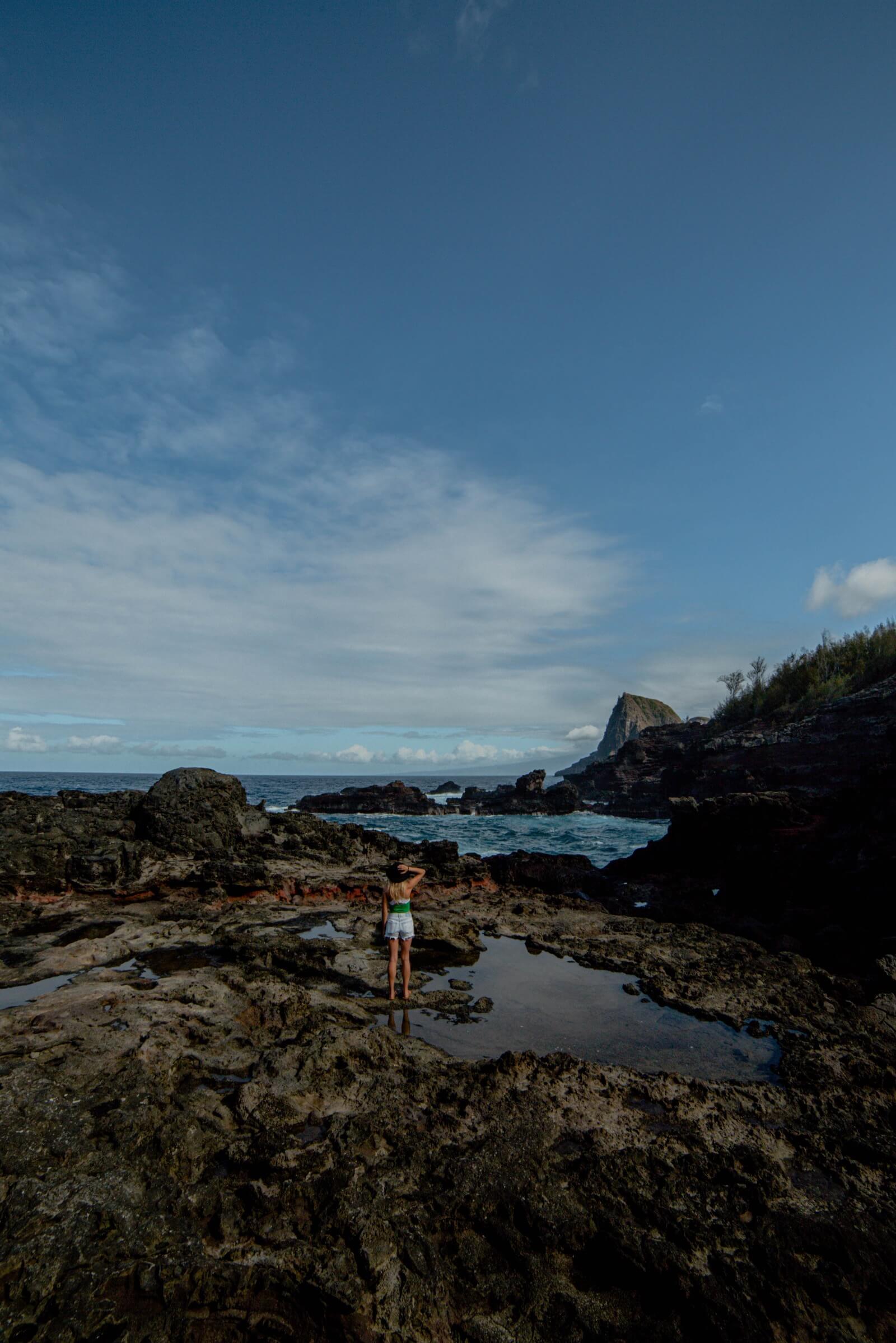 Girl standing on rocks near the ocean at Olivine Pools